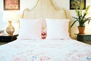 An upholstered headboard with nailhead trim paired with patterned bedding
