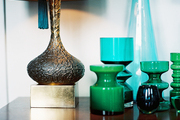 Green vases and a lamp atop a wooden cabinet