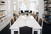 A white rectangular dining table paired with brown chairs and open shelves for storing serving pieces