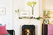 A bust and framed art on a white fireplace mantel