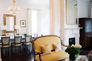Antique crystal chandeliers and upholstered furniture in adjoining living and dining spaces
