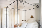 A canopy bed dressed with white linens
