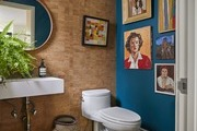 blue and cork tile powder room with vintage gallery wall of portraits.