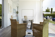 Square wicker chairs atop striped rug in white living room.