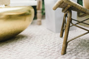A detail of a chair leg and a gold coffee table on a Bohemian rug.