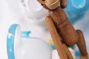 A wooden monkey beside blue teacups and a teapot