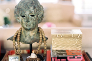 A tray topped with a bust decorated with a string of beads