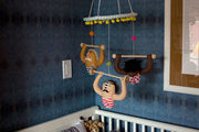 A mobile hangs over a baby's crib