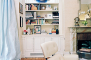 Blue curtains and brick floors in a family space with built-in bookcases