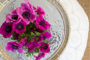 Colorful flowers and silver dish atop white stool.