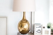 A detail of a neutral nightstand with gold lamp.
