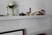 A shelf with sentimental knickknacks in a white-walled living room