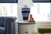 A sunroom designed by BHDM features roman shades with greek key trim and oversize furniture in green and blue.