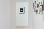 A white hallway with a gallery wall.