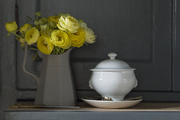 A gray pitcher with yellow blooms next to an ironstone china vessel