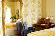 A yellow, floral wallpapered master bedroom in New Orleans