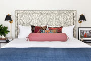 A contemporary bed with patterned headboard and red pillows.