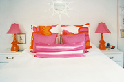 A white bedroom with orange and pink lamps and pillows