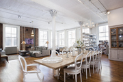 Large natural wooden table with white chairs in large open dining area.