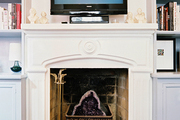A TV surrounded by miniature busts on a white mantel