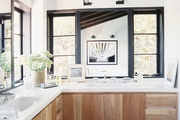 Wood cabinets and a white marble counter in a light-filled bathroom
