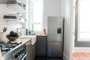 A contemporary kitchen with white subway tile and open shelving.