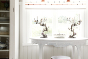 A wooden stool and a white table set in a sunny window