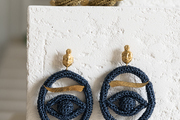 A pair of earrings hanging on a display table.