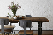 A white brick wall is the backdrop of a long, rustic farm table