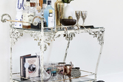 A bar cart sitting on top of a patterned rug with various bottles, shakers, and drinking glasses.
