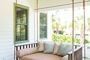 A lounge on a swing on a porch outside of a white and green house.