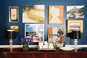 A grouping of art hung above a dining sideboard topped with a pair of lamps
