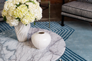 White hydrangeas on a marble-topped table and area rug at Jessica Alba's Honest Company office