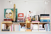 A shelf styled with books, art, and glass objects