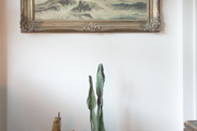 A framed painting above a grouping of potted cacti
