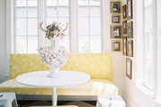 A yellow banquette in a kitchen nook