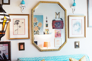 A gold mirror hung above a bench covered with patterned blue fabric