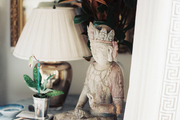 A small statue and a mirrored lamp atop a round marble-and-wood side table