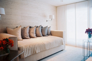 Grass-cloth wallpaper paired with an upholstered daybed