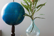 A towering flower and a celestial globe on a rustic wood side table