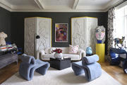 Contemporary living space with vintage velvet furniture, wall art, and sculptures
