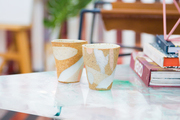 Ceramic tumblers on a coffee table.