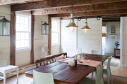 A rustic dining room features exposed beams and pendant lights