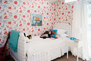 A white upholstered bed accented by floral-patterned wallpaper and a blue throw