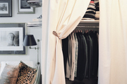Flowing white curtains in front of an organized closet