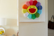 A cartoon flower sitting in a picture frame against the wall.