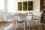 An eclectic mix of white chairs surrounding a round dining table