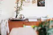 Artistic photography and flowering branches in a dining room, grounded by a midcentury sideboard