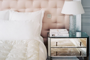 A mirrored bedside table paired with a tufted headboard
