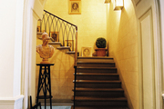 A staircase decorated with a potted boxwood and framed art